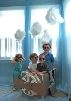 "Airplane Birthday Party Ideas - savenger hunt & cardboard airplane, blue sky with clouds photo op - Each child had to find four ""pilot tools"" to put in their ""pilot bag"": a compass, a propeller, a parachuter, and a map.  Once they had all four items they each received their own pair of pilot aviator glasses and they posed for a picture together."