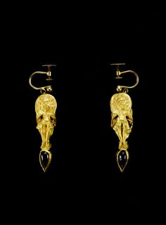 A pair of Hellenistic gold and garnet Erote earrings. Circa 2nd-1st Century B.C.