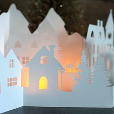 This winter village has a mountain scape in the background with little village houses, clock towers, light poles and trees in the front two layers.