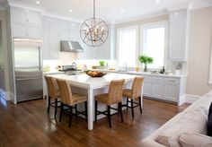Very simple kitchen island with a clean, white design and a table for four