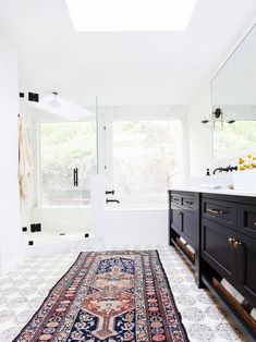 Handmade tiles from Tabarka Studio add pattern into the otherwise neutral master bathroom. Idea to steal: Forgo your standard bath mat for a far more interesting Persian rug.