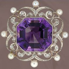 Platinum over 14K yellow gold brooch highlighting a magnificent octagonal cut amethyst (22.00 carats) surrounded by a delicate openwork frame of scrolls set with twenty old mine cut diamonds (.50 carat total weight, G-I color, SI-I1 clarity) and accented by eight seed pearls (3.50 mm). This pin measures 1 1/2.
