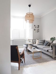 A light, scandi-style living room with painted white floorboards and a grey corner sofa