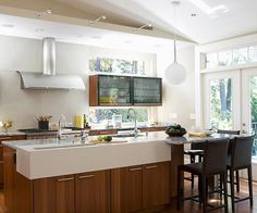 Is this kitchen more modern or minimalist-retro? I love the clean lines, the glass cabinets, and the seating at the end of the island. I would also love to have the large commercial stove, two sinks and all those windows!