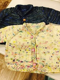 Top down raglan baby cardigan sweater with small roll collar and seed stitch detail at cuffs and hem. Easy and quick to make for any new addition.