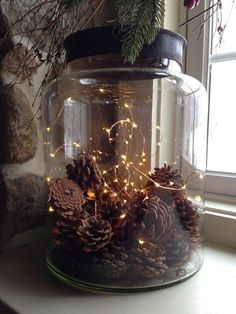 Love this rustic mason jar with pine cones and fairy lights.