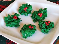 """HOLLY COOKIES: makes 2 doz.   Melt 1/2 cup butter and 30 large marshmallows, stirring constantly. Add 1/2 tsp. vanilla and 1- 1/2 tsp. green food coloring. Mix in 3 - 1/2 cups corn flakes. Grease a spoon and drop mixture onto veg. oil sprayed wax paper. Place 3 red cinnamon candies on each bunch of """"holly,"""" pressing slightly so that they stick.   Let sit until they have hardened."""