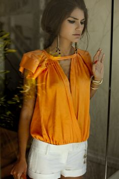 where can I find that blouse? damn. bright orange top, gold accents, classic white shorts