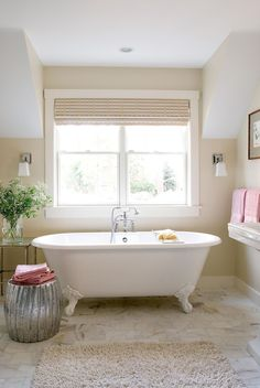 This neutral bathroom matched the beige paint to the floor's marble tile, then added subtle silver accents for a little bit of glam. Blush-pink accents keep the space cheery and warm. #bathroomideas #bathroomcolorschemes #beigebathrooms #bathroomdecor #remodel #bhg