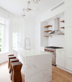 marble waterfall island, white cabinets and warm wood ...perfection!