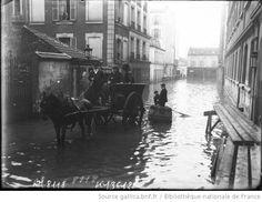 31-1-1910, rue Lacordaire [inondations à Paris, 15e arrondissement, passage de personnes en charrette et sur une barque] : [photographie de presse] / [Agence Rol]