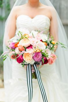 Bright and beautiful bouquet, full of dahlias, garden and sweetheart roses, ranunculus, anemones, and stock blooms. Designed by Hey Gorgeous Events.