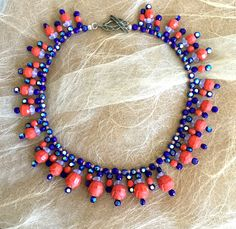 "Coral and Cobalt Cleopatra Collar This one of a kind piece is made up of beautiful vintage glass beads in gorgeous coral and cobalt colors. The coral beads are very rare and are from a signed Vogue necklace from the 50's. They are shiny faceted on the tops and mat around the carved petals. The cobalt beads are iridescent on one side. 18"" long and center drops are 1.25"". This piece has a beautiful sterling filigree leaf clasp."