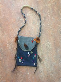 Dit is een modeproduct. De opdracht was om iets origineels te maken. Ik heb voor een tas gekozen. Ik heb de tas van spijkerstof gemaakt. De vorm is simpel maar de details niet. Die bestaan uit gevlochten paardenhaar staartjes, knopen en ook een paar veren. Het handvat bestaat uit dit touw.