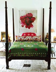 If ever I wanted a four-poster bed, this would be it. The dark wood combined with the white walls and floor together with the green bedspread and the red-and-white art work make a really beautiful bedroom.