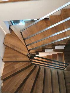 Halbgewendelte Faltwerktreppe Eiche, Stufenstärke 80 mm. Im KG Stufenbelag in Eiche als Faltwerkausführung auf 1/2 gewendelter Betontreppe. Edelstahlgeländer aus Flachstahl 40x8 mm gerade mit 4 Gurten incl. Handlauf. #DiseñoDeEscaleras