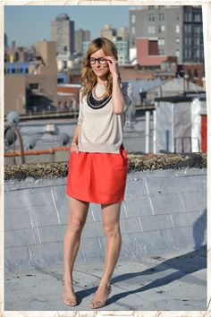 Um, I love all of this. Chunky necklace, sparkly sweater, orange skirt, nude heels -- want!