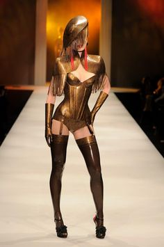 Atsuko Kudo Latex.   A fully gold lace printed outfit turned heads as our 12th look on the catwalk! The look features a Tassle Cape worn with a Candy Cup Corset and High Waist Briefs, Seamed Stockings, Tassle Alejandra hat, Tassle Earrings and Handcrafted Gloves. Image by Andrew Lamb