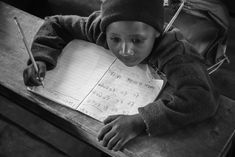 """Mama said don't give up."" A black and white portrait of a cute Maasai student working on his spelling task in his class."