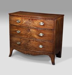 George III mahogany bowfront chest of drawers. Crossbanded top with tulipwood inlay over three graduated cock beaded drawers with fantastic colour and flame figure. Fitted with brass plate handles and raised on shaped splay feet. circa. 1800 £1,950