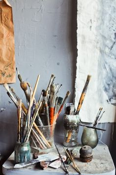 A variety of jars and bottles containing brushes and art supplies