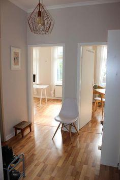 Lichtdurchfluteter Flur mit modernem Stuhl und schöner Lampe.  Wohnung in Hamburg. #Einrichtung #Flur #hallway