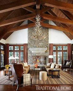 Love this two-story stone fireplace and exposed rafters. Sophisticated Family Cabin in the North Woods | Traditional Home
