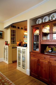 Work in the kitchen eliminated the plethora of non-supporting columns; glass-fronted cabinets now divide the kitchen and dining room.