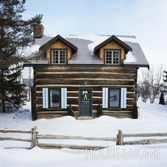 Designer Kate Thornley-Hall's 100-year-old log cabin is a winter haven with its quaint shutters, cedar dormers and classic evergreen wreaths. | Photographer: Angus Fergusson