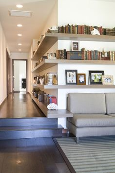 wrap around built in shelving in the hallway becomes an end table and picture rail above the sofa