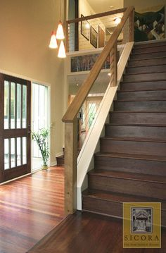 Wood and cable railing. nice and clean, not too modern that it is out of place, but not the horrible traditional stair rail.