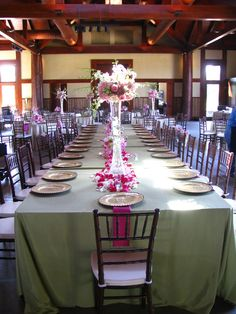 Tall glass floral centerpiece on banquet table.