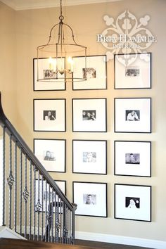 Stairwell landing features light camel colored walls lined with a black and white photo gallery wall illuminated by a Currey and Company Fitzjames Lantern Chandelier.