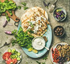 #Summer barbecue party dinner set  Summer barbecue party dinner set. Flat lay of grilled chicken skewers with yogurt dip flatbreads parsley vegetables marinated olives and chilis over grey concrete table background top view