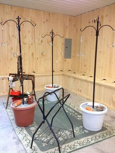 Pots filled with concrete with hangers to hold tack hooks. On the concrete is the cleaning supplies. Neat idea from Huntington Meadows in Rochester, NY
