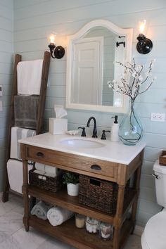great sink with shelves instead of drawers, black faucet, light blue walls, black sconces on either side of mirror. LOVE this bathroom!