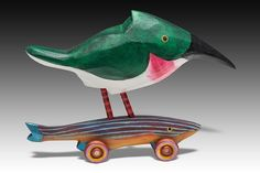 Texas Kingfisher Rides the Minnow by Dona Dalton. From northern South America up to Texas and New Mexico, the feisty Green Kingfisher will hover and dive. This time, she's landed on a fish, not necessarily for a meal. Prawns and insects are good too. Band saw carved poplar, with acrylic and latex enamel paint. Fish patterns and wheels may vary.