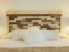 This rustic-chic headboard was made from an old picket fence. The pickets were cut up into small pieces, cleaned and then refinished in a few different stains. Then the pieces were fitted into a frame made from more weathered lumber.