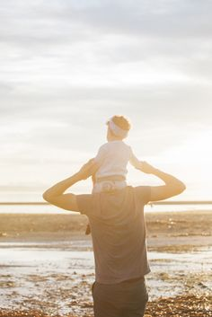 Dad carries his toddler daughter on his shoulders on the beach at sunrise. Family photography by Monashee Photography.