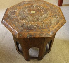Small octagonal oriental table with gilt inlay and Moorish influence carved base. Height measures 12 inches, width across the flats measures 11 inches. Some loss to the gilt inlay on table top. Base can be removed and folded with set of hinges jointing the flats of the base support.