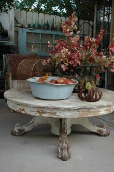 Beautiful round oak claw foot table with a white chippy finish.