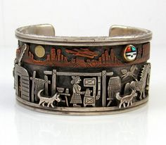 This wonderful work of art, by the ward winning father and son duo Clarence and Russell Lee (1970s), depicts the Native American Indian farm life, sculpted out of sterling silver with gold and brass toning to accent the sun/moon and surrounding mountains, finished with a hand stamped design along the edge of the cuff bracelet. Also featured is a Sunface applique, featuring coral, turquoise, black jet, and mother of pearl shell.