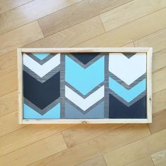 This hand painted chevron wood sign is 21.5X11.5. Granite gray, white, medium gray and whispering turquoise chevrons with a natural wooden frame.
