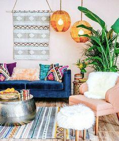 ein bunt gestaltetes Wohnzimmer mit blauer Polstercouch, bunten Kissen, Musterteppich , Designer Couchtisch