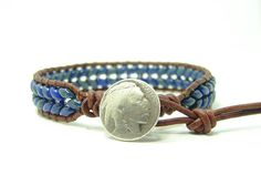 This single wrap bracelet is made of 2 1/2 x 5 m Dark Blue Picasso Superduo beads woven with the herringbone stitch on a distressed leather cord using a silver metal button for the closure. The bracelet has two loops and measures at 7 1/4 & 8 1/4 from the loop to the button and approximately 7/16 wide. The bracelet in the picture has been sold. Yours will look a little different due to the picasso finish on the beads. If you need a different size, let me know at check ...