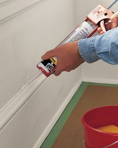 To fill cracks between the baseboard -- or any trim -- and the wall, apply latex caulk (which can be painted) with a caulking gun, following the manufacturer's instructions.