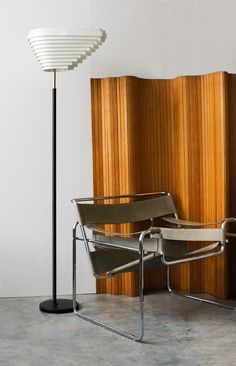 ALVAR AALTO, Floor lamp, model A805, also known as the Angel Wing. Originally designed in 1954 for the National Pensions Institute in Helsinki. Distributed by Artek Oy, Finland. Pine wood screen also by Aalto, model 100 (1936).