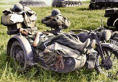 In a wheat field, most probably on the Eastern front's southern sector, an exhausted German soldier from the 11th Panzer 'Ghost' Division rests on his Zündapp K800/sidecar combination, his sleep...