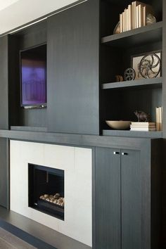 Suzie: Kelly Deck Design - Ebony wood built-ins, sliding door TV cabinet, TV and fireplace.
