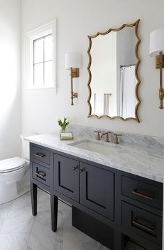 Antique Br French Sconces Flank A Gold Leaf Vanity Mirror Hung Over Black Washstand Accented With Pulls And White Gray Marble Countertop
